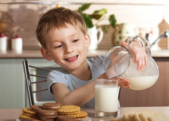Ребенок наваливает молоко из кувшина